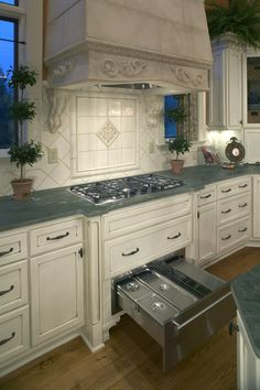 Traditional kitchen with high ceilings, a custom tile backsplash, marble counters, undercabinet lighting and gorgeous hardwood floors. Click on the image to see how you can install kitchen counters. #traditional #warmingdrawer