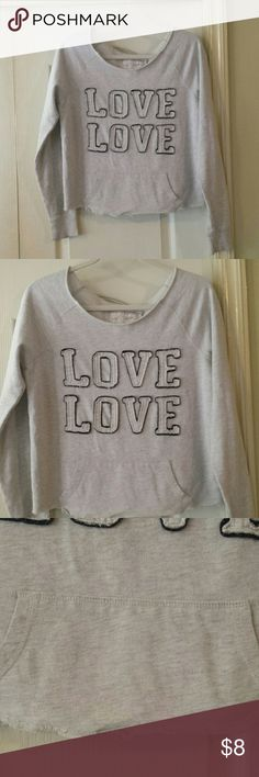 """Cute Distressed """"Love"""" Sweatshirt. Size Medium. Grey distressed sweatshirt with """"Love"""" outlined in black with threads hanging from it. It has a raw neckline, raw hem, & a hole in the left shoulder (pic 7), which was there when I got it. Part of the distressed thing, I guess. No stains. Very comfortable! Cute with jeans or shorts and super cute over a bikini with denim shorts at the beach. Size medium. Approximately 21"""" long from top of shoulder to bottom of raw hem. Not short enough to be a…"""