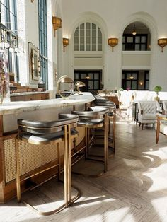 Classic eclectic resturant and bar with white marble + black and brass seating + herringbone floors + black accents