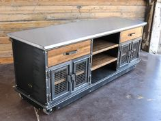 Large Boxcar Ellis Console with a Stainless Top  Model #E46  This piece has a stainless top with matching corner rivets, 2 top drawers, 4 doors with woven wire mesh, and reclaimed boxcar oak shelves.
