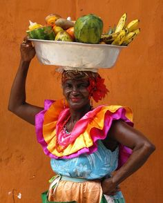 Who wants some tropical fruits? ;) This lady works in Cartagena's old town offering fruits, due to her picturesque look she is regularly photographed by tourists, which became part of her daily job. She wears typical folkloric outfit from the caribbean coast of Colombia #discover #cartagena #colombia