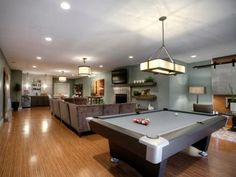 The sophsticated space has a clever layout with divided areas for serving snacks, watching TV and playing games. Lighting and neutral, monotone colors makes the basement hangout open and bright.