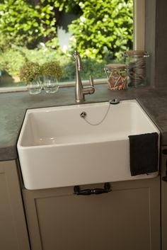 Wasbak in een keuken met betonnen aanrechtblad.