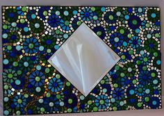 A 24 x 16 mosaic stained glass mirror with alot of tiny pieces. There are pieces of mirror that catch the light and spread tiny reflections