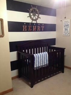 Navy White Nautical Nursery With A Painted Stripe Wall Behind The Crib