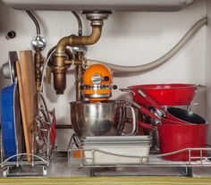 Pots, pans, and a mixer under sink on roll-out shelves