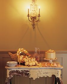 The cornucopia, that traditional symbol of fall's abundance, assumes a stately presence, thanks to a coating of shimmering floral spray and a wreath of gold-leafed oak leaves and acorns.