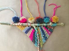 Take an ordinary branch from outside, paint it, add yarn, beads, and pom-pons, and now you have a beautiful weaving that you can hang on your wall.
