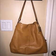 "Coach leather handbag in the style ""Phoebe"" authentic coach leather shoulder bag, I believe the color is burnt camel. only been used a couple times. there is a little spot where the leather came off & another spot where something got on it, not quite sure what happened, I'm selling it for a friend. if you'd like to see the blemishes, let me know & I will upload pics. it has three pockets total, 1 on each side that clasp together & 1 in the middle that zips close. all zippers & clasps 100%…"