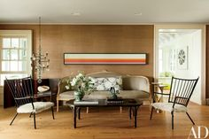 The living room, sheathed in a Roger Arlington grass cloth, features a Kenneth Noland painting, a 1770 gilt-wood sofa, a vintage hanging candelabra by Erik Höglund, and 1950s French armchairs   archdigest.com