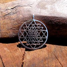 """Yantra is a mystical hindu concept that describes a structure or diagram used to balance or focus the consciousness in order to achieve spiritual comprehension.     The SriYantra is a structure made of nine triangles tied to each other surrounding a center point called a """"Bindu"""". The structure of the Sri Yantra pendant is one that provides abundance, beauty, and balance between male and female."""