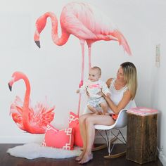 Two large pink flamingo wall decals in different positions on a white wall behind a mother and baby sitting on a white chair. One flaming is standing and the other is sitting.