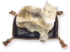 A ROCK CRYSTAL AND AMETHYST CAT, BY BOUCHERON  The carved rock crystal cat with mother-of-pearl and black onyx eyes, resting on a carved amethyst pillow, enhanced by two color gold braided detail and tassels, mounted in 18K gold