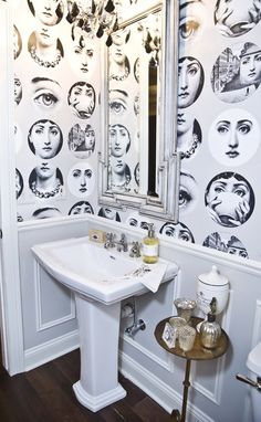 EDGY BLACK-AND-WHITE BATHROOM  The vintage face pattern, crystal and black chandelier and uniquely framed mirror come together to create an edgy glam bathroom.
