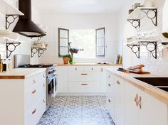 Bright kitchen with blue printed tile floors, wood countertops and floating shelves