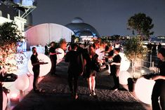 Following the screening, guests headed upstairs to the open-air flight deck, where illuminated spheres and potted trees lined the pathway...