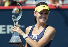 Agnieszka Radwanska of Poland holds up the winner's trophy after beating Venus Williams of the United States in the final at the Rogers Cup 2014