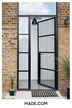 A warehouse entrance never looked so good. This conversion has tall glass-paned doors with black trim making the hall bright without taking away from the building's charm