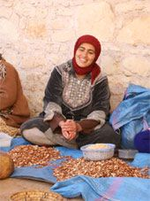 A woman working with argan nuts who is part of a co operative of women #ArganOil manufacturers