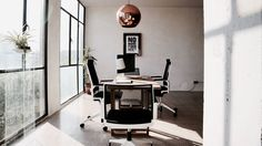 Modern designer home office / coworking space with full height iron windows, Tom Dixon lamp, framed artworks, oak desk and white Dynamobel office chairs. Location: Studio Zamora Barcelona