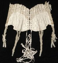 Woman's Wedding Corset with Garters    Made in New York, New York, United States  1903    Made by Binner, New York. Worn by Mrs. Henry Frazer Harris, née Virginia Blair Johnston.    Off-white silk damask, lace, pale green elastic, off-white silk ribbon, artificial orange blossoms  26 x 13 inches (66 x 33 cm)
