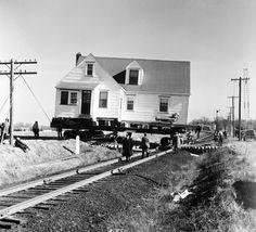 Groupe d'hommes déplaçant une maison sur roues sur les voies d'un chemin de fer, 1960.