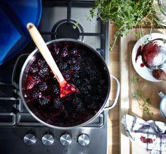Blick auf SENSUELL Topf mit Deckel aus Edelstahl auf einem Kochfeld, in dem gerade Brombeeren zu Marmelade eingekocht werden.