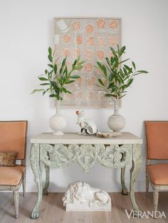 On the landing, an English console table is flanked by chairs that once belonged to Cole Porter, in their original pink silk velvet. Painting, Corey Daniels.   - Veranda.com