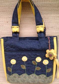 Bolsa confeccionada em jeans, tricoline e algodão, forrada com manta acrilica e tecido de algodão, bolsos internos, ziper, apliques bordados nos dois lados da bolsa. Quiltada, frente, verso e bolso.  Ótimo acessório pra o seu dia-a-dia!  1 chaveiro de brinde.  (cada bolsa é única por isso pode te...