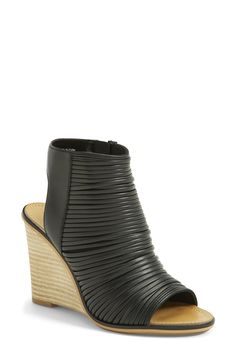 Overlapping black faux leather straps define a chic bootie set on a curvy wedge heel.
