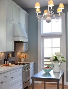 kitchens - white kitchen cabinets marble countertops gray subway tiles backsplash stainless steel island appliances chrome hardware white chandelier blue gray walls paint color kitchen, white hood - unusual!  Inset shelf in backsplash over slide in range
