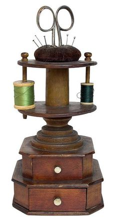 Turned and carved wood sewing Stand with two drawers and spool holders with a brown velvet pincushion on the very top.