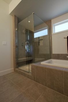 Neutral tile covers the floor in this beautiful modern bathroom. A large, walk-in shower is surrounded by glass revealing the neutral pebble flooring, built-in shower storage shelf and rain shower head. Next to the shower, a white bathtub allows for relaxed soaking in the calm room.