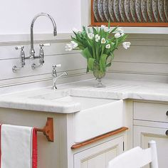 To enhance the farmhouse feel of an apron sink, top the sink cabinet with a wood shelf before installing. The resulting touch of wood makes it look like the sink is set on a table. | Photo: Paul Zammit/IPC images | thisoldhouse.com