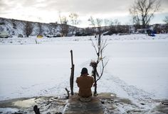 Army veteran Nick Biernacki, of Indiana, prays at the Cannonball River at the Oceti Sakowin camp where people have gathered to protest the Dakota Access oil pipeline in Cannon Ball, N.D., Sunday, Dec. 4, 2016.