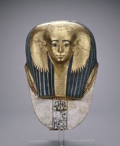 Mummy mask, Early 18th Dynasty Ancient Egypt, 1500 BCE. Cartonnage mummy-mask of Satdjehuty: on this splendid female mask, gold leaf not only covers the woman's face, but also her huge collar necklace and the vulture-headdress that embrace the front and sides of her voluminous, lapis lazuli-coloured wig. The wings are examples of protective symbolism that evokes the guardianship of Isis and other deities.