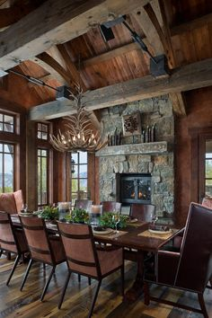 Big Sky Journal - The formal dining room is scaled-down to encourage intimate conversations among guests at the harvest table. Elk horn chandelier by Fish Antlers, rolled leather chairs by Hickory Chair Company.  #mountaincabin #rusticdecor