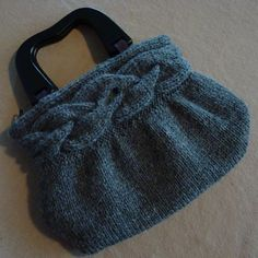 Cable Band Bag on Ravelry. Could be super cute as a clutch without the handles.