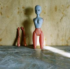 Color photo of an armless doll, turning her back to a wooden panel, variously scraped