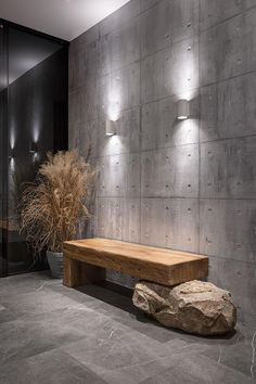 This modern entryway has an exposed concrete wall highlighted by two wall scones, and features a wood bench that rests on a boulder.