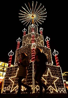 Two women walk in front of a Christmas illumination at a Christmas market in Berlin. (Photo by Markus Schreiber/Associated Press)