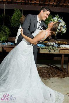Noivo segurando a noiva para beija-la