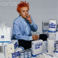 Public Image Limited's John Lydon smokes a cigarette while surrounded by generic paper products and foods 1986 | Photographer Jackie Sallow.