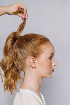 Step Three: Separate a piece of hair from the ponytail and wrap hair around the elastic band. Pin the wrapped hair to the underside of the ponytail.