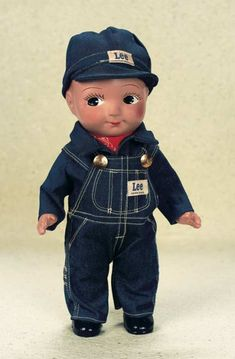 "American Composition ""Buddy Lee"" with Original Labeled Uniform 13"" (33 cm.) One piece composition head,torso and legs with chubby shape,jointed composition arms,painted brown hair in side-swept fashion,painted large black side-glancing eyes,long lashes,button-shaped nose,closed mouth with impish smile. The doll is wearing his original red bandana,denim shirt,overalls and cap,with Lee labeled brass buttons,and ""Lee Union Made"" labels on the front and back overalls and cap. Circa 1930,the…"