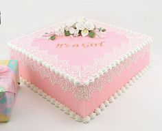 ~sheet cake formal with It's a Girl and small bouquet of flowers/  piping and appears to be lace around the edges
