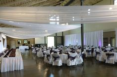 White Ceiling Drape, White Pipe & Drape, White Door Drape, White Chair Covers with Raisin Organza Sashes (traditional bow), White Table Linens, Raisin Satin Runners, Silver Charger Plates, Raisin Napkins (pyramid fold) and Uplights at Gale Woods Farms by Deckci Decor
