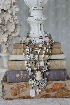 Necklaces on books two of my favorite things! Would make a great jewelry display for the vintage flea market