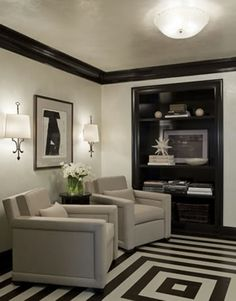 Black and White rug or painted floor.  Black and white abstract art.  Wall sconses and metallic cieling.