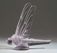"""This car mascot, """"Libellule,"""" is the one formerly used by acting legend Gary Cooper on his Duesenberg. The mascot is in clear and frosted glass with a pale amethyst tint, molded R. LALIQUE FRANCE and engraved R. Lalique France, standing 8 1/4 inches tall."""